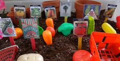 Spring sensory bin with plastic fruits and veggies, flower pots and fabric flowers, coffee beans or potting soil, etc.