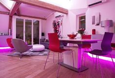 Pink neon lights provide a wonderful glow to this contemporary living / dining room