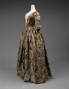 1735. British. Side front view. Heavy Spitalfields silk with lace pattern design woven in beige and rust on a dark brown satin ground. No signs of alteration.  (C.I.64.14).