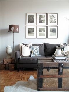 why I love it: gray couch with wood floor, vintage artifacts all over, black and white photography on the wall