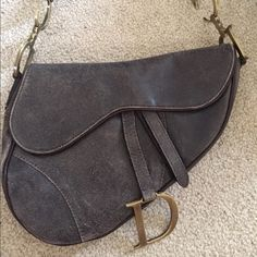 """CHRISTIAN DIOR Leather Saddle Bag Taupe/Brown distressed leather Christian Dior saddle bag with gold tone hardware, flat shoulder strap, brown woven interior lining, single zip pocket and Velcro closure at front. Includes dust bag and authenticity card. Excellent condition. Light wear to leather. Shoulder strap drop 7.5"""". Christian Dior Bags Shoulder Bags"""