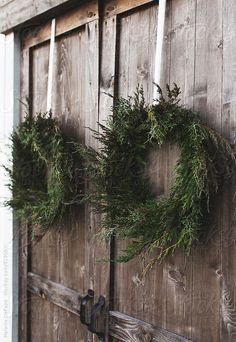 Beautifully made natural pine and cypress wreaths hanging on barn doors for the holiday season providing rustic christmas inspiration and Scandinavian christmas ideas for the holidays wreath creative