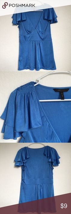 BCBG maxazria blue ruffle sleeve v-neck blouse Beautiful blue color blouse with ruffle detailing on the sleeves and a v neckline. Flattering flowy bottom of the blouse. Size large (I held it in the back for the photo). Firm price. BCBGMaxAzria Tops Blouses