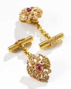 A pair of jeweled varicolor gold Fabergé cufflinks, workmaster August Hollming, St. Petersburg, 1898-1904, the links formed as Imperial double-headed eagles set with diamonds and centered with a cabochon ruby, the bars with diamond-set ties.