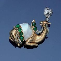 A diamond and gem-set brooch, by Verdura, circa 1952 The seated camel with baroque pearl sadle with cabochon emerald highlights and a seed pearl bridle and fringe, wearing a headress of brilliant and single-cut diamond plumes with a cultured pearl highlight, signed Verdura, minor damage to seed pearl fringing, length 3.9cm.