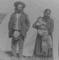 A photograph of a Metis? man with a Cree? woman and her child standing outside a teepee. Picture possibly taken by George Mann family who worked with Cree people in Onion Lake, Saddle Lake and Hobbema reserves between 1883 and 1916.
