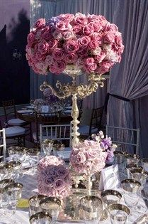 An opulent silver candelabrum crowned with pink roses stands out among small vases of roses and silver-rimmed glassware.