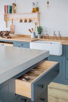 Industrial Shaker Style showroom kitchen with oak cabinetry. The base cabinets are hand painted in Farrow & Ball Down Pipe and have an oak worktop. The shelving is a birch shaker peg shelf and open oak drawers are visible below. The island has a polished concrete worktop and the Shaw's farmhouse sink with double Perrin & Rowe taps offset the colours beautifully.
