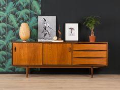 Klassisches Sideboard aus den 1960er Jahren im skandinavischen Design. Korpus in Teak Furnier mit zwei Schiebetüren, drei Schubladen und zeittypischen, spitz zulaufenden Füßen. ...