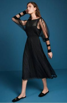 Georgette stripes and insets of delicate, sheer point d'esprit add rich texture and an air of romance to this delightful little black dress styled with a daring open back and a demure midi-length skirt.