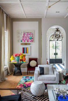 Living - Paola Ribeiro. As cores são uma marca do projeto, com branco, preto, cereja, verde, amarelo e azul. Junto com a base neutra, elas revigoram a construção sem abrir mão dos elementos arquitetônicos originais.