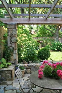 Garden with a stone and wood pergola, seating wall, terrace, lawn, and lush border