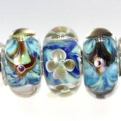 Trollbeads Gallery - Trio Just Listed with 2 Fish beads and a glitter flower bead. All sharing the green/aqua watery base. http://www.trollbeadsgallery.com/twins-trios-290/