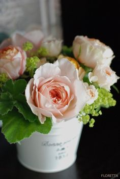 pink roses in a white tin floral arrangement