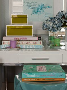 stack of coffee table books, desk, flowers & vase
