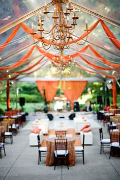 Tented event space w/ tangerine accents, clear roof w/ chandeliers, Enchanting Events