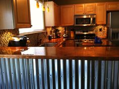 Copper bar top with corrugated metal sheeting on the sides.