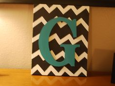 Paint chevron design on canvas using painters tape, paint wood letter and glue onto canvas