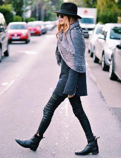 Black boots, black leather skinny, black oversized jumper, black hat, grey scarf worn over the shoulders like a cape.