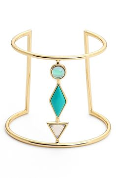 A turquoise-hued enamel stone sits between two geometric-shaped crystals, adding Southwestern charm to this statement-making cuff.