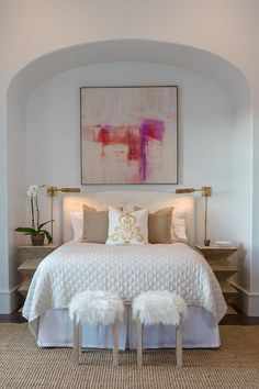 Chic bedroom boasts an arched nook filled with a pink and purple abstract art piece placed above a white tufted curved headboard on bed dressed in white and tan bedding flanked by light taupe geometric accent tables as nightstands illuminated by Studio Swing Arm Wall Lights.