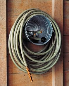 A galvanized paint bucket makes a practical and inexpensive caddy for a garden hose and sprinkler.Drill three holes in a triangular pattern in the bottom of the bucket. Depending on your wall, bolt or screw the bucket to the wall; strengthen the cut edges of the holes with washers.