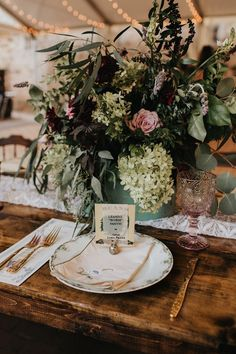 Watering can + floral centerpiece with light pink glass, vintage plates, gold utensils, and personalized seed packet | Image by Tree of Life Films & Photography