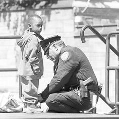 Black And White Photo Of A Police Officer Kneeling Down To Tie A Little Boy's Shoe At A School.