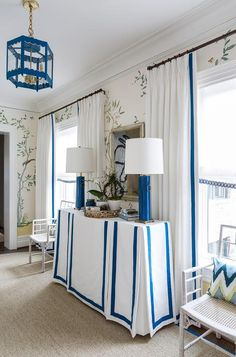 Whimsical hall features walls clad in chinoiserie wallpaper lined with a white and blue skirted console table topped with sapphire blue column lamps under a mirror flanked by windows dressed in white curtains accented with blue ribbon trim illuminated by a blue pagoda lantern.