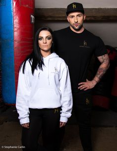 Model 1 wears white over head hoodie with black embroidered S.H exercise leggings. Model 2 wears black Sydney Harper tee shirt with black S.H embroidered track trousers.