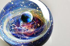 宇宙をイメージしたペンダントトップ「宇宙ガラス」が、幻想的で美しいと話題になっている。「宇宙ガラス」は、アクセサリーブランド「+α」の作品で、宇宙を球体のガラス
