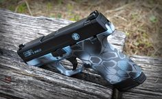 Smith and Wesson M&P Shield 9mm. Kryptek pattern done in Cerakote Custom Blue mix, Graphite Black, Tactical Grey and Battleship Grey.