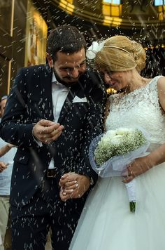 Groom and his bride getting ''showered'' with rice for blessing and happiness. Wedding by weddingskyros.com in Athens