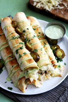 Slow Cooker Jalapeño Popper Chicken Taquitos - chicken - cream cheese - jarred whole or sliced jalapenos - garlic powder - salt - cumin - flour or corn tortillas - shredded Colby or Monterey Jack cheese - optional - cilantro - jalapenos - salsa - tomatillo