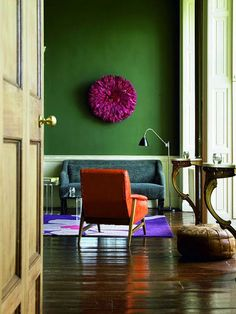 Love these Feathered African Jujus - really adds a pop of color and texture. Love this wall colour! Bold!