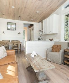 The full kitchen has whitewashed cabinets, a freestanding range with venting hood, refrigerator with bottom freezer, and a deep single bowl sink. Next to the kitchen is a dining table with room for six.