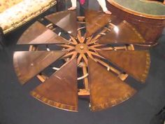 """Expanding dining table. The ingenious Robert Jupe table mechanism enables a round table to grow in diameter from 60"""" to 84"""" by the insertion of eight dart-sh..."""