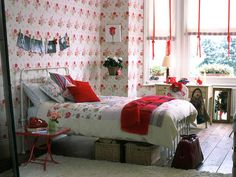 Rose-patterned wallpaper and textiles get a youthful lift with the help of red and blue accents -- #girly #floral #decor