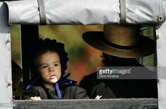 News Photo : An Amish girl looks out of the back of a...