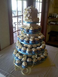 wedding cake with lilies and cupcakes. I like the idea of adding two tiers for the cake and the 3rd tier/ 4th tier being cupcakes. I also like the wedding colors being tied in by having them holding the cupcakes