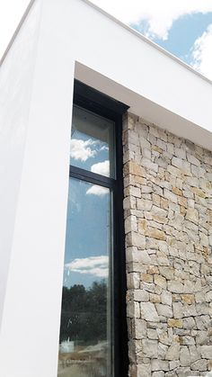 Chiralt Arquitectos I Ventanal moderno contra muro de piedra y revestimiento de estuco a la cal minimalista.