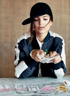 Emily Ratajkowski wears a collared shirt, bomber jacket, and baseball hat for Vogue photographed by Theo Wenner