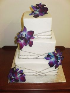 3-tier square cakes finished in white buttercream with silver striping. Fresh purple dendrobium orchids accent the corners and top of this cake.