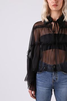 Romantic with a bohemian flair, this sheer blouse features billowy ruffles and ties at the neckline - tie as loose or as tight as desired to alter how oversized