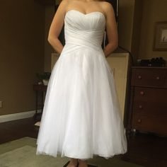 Wedding dress. Strapless Tea Length A lovely strapless tea length wedding dress. Pure white in color. Never been worn other than trying on. Strapless sweetheart tulle. Tags still attached. David's Bridal Dresses