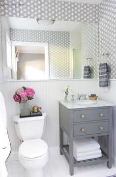 Ideas and inspiration for remodeling a small bathroom: gray vanity with marble top and Delta Cassidy chrome faucet | Cayman Cork Wallpaper via Serena & Lily | Image via Driven by Decor