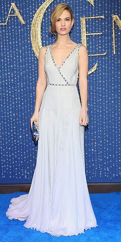 "Lily James's Magical Red Carpet Moments: See All the Cinderella Star's Chic Looks | PRADA PRINCESS  | Lily must be resisting the urge to twirl around in her plunging, ice-blue, chiffon Prada gown featuring embellished piping. She accessorizes with delicate jewels, an Anya Hindmarch ""Crisp Packet"" clutch and a gorgeous pony at the Mexico City premiere."
