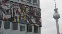 De Fernsehturm verschuilt zich achter een kleurrijk kunstwerk uit mozaïek.