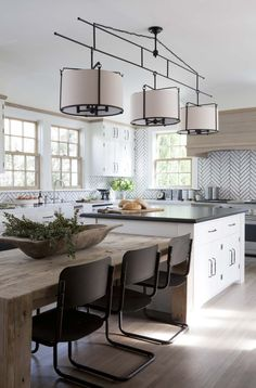 Love the reclaimed wood dining table as an extension to the island.  The chandelier spans both areas making it once cohesive space.  Beautiful backsplash and touches of drifted wood in the range hood, window frames, crown moulding.