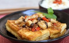 In this dish, tofu is stir-fried until golden and served in a thick umami-flavored sauce. It's garnished with baby king oyster mushrooms and goji berries, both of which are pan-fried in a homemade sauce for added flavor